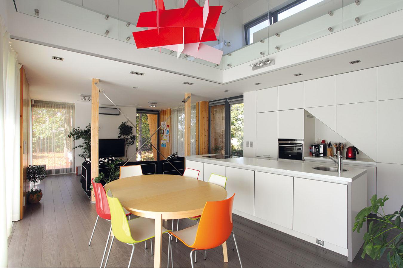 """Vnútorné zariadenie domu dotváralo interiérové štúdio, ktorého architekti excelentne """"uchopili"""" architektonického ducha stavby avsúlade sjeho odkazom na funkcionalizmus vytvorili modernistický, čistý ajasný priestor. Dominuje vňom racionalita abiela farebnosť, zjemnená prvkami viditeľnej drevenej konštrukcie adrevenej dlážky. Potrebné rozveselenie celku sa dosiahlo pestrofarebnými dizajnérskymi kúskami (luster, stoličky) vjedálenskej časti."""