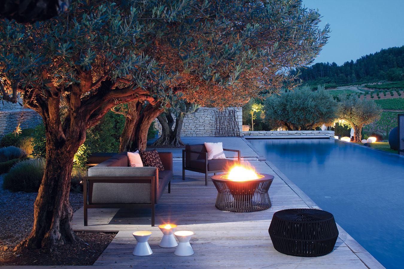 Doplnky môžu hrať na terase aj v okolí bazéna dôležitú úlohu a priestoru dodať výnimočný šarm. Lampáše, olejové lampy, veľkorozmerné kvetináče, ktoré štýlovo (a materiálovo) harmonizujú so zvoleným záhradným nábytkom, či dokonca ohnisko. Zaujímavú ponuku nájdete v sortimente značky Kettal. (Predáva Konsepti.)