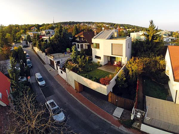 Od ulice delí dom okrem vytvorenej malej záhrady aj výškový rozdiel, ktorý zabezpečuje dokonalé súkromie obyvateľov.
