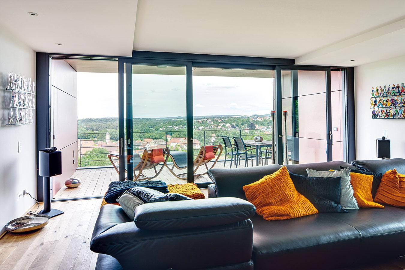 Bez prekážok. Na poschodí majú majitelia obývačku spôsobivým výhľadom do údolia, na ktorú nadväzuje terasa. Zasklený fasádny systém tu búra hranice medzi vnútorným avonkajším priestorom nielen vizuálne, ale aj funkčne – vďaka veľkým posuvno-zdvíhavým dverám ich za pekného počasia možno dokonale prepojiť.