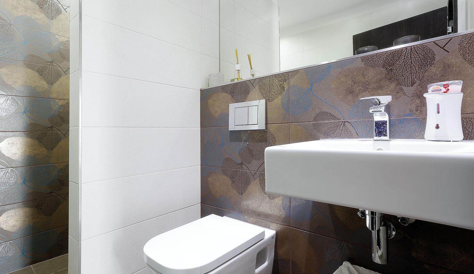 Priestor kúpeľne oživuje zvolený viacfarebný vzorovaný obklad stien, ktorý príjemne dopĺňa bielu sanitu.