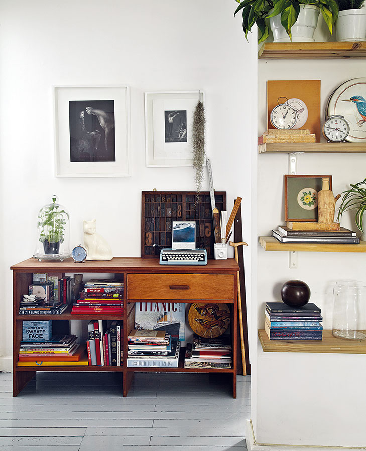 Miesto na spomienky. Police ukotvené priamo v stene obývačky a nízka skrinka v štýle vintage sú miestom pre rastliny v jednoduchých bielych kvetináčoch a pozoruhodné úlovky z blších trhov. Zarámované obrazy nad skrinkou sú dielom juhoafrického výtvarníka Michaela Taylora.