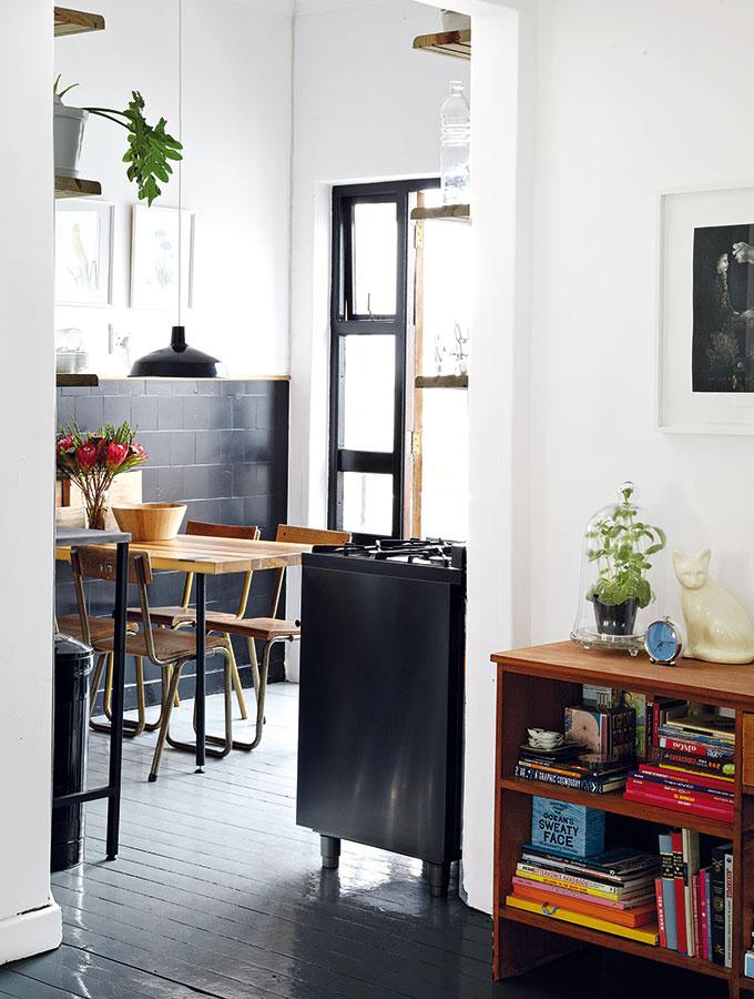 Pohľad z obývačky do útulnej kuchyne, ktorej dali tmavosivé obkladačky novú estetickú kvalitu. I keď miestnosť nie je veľká, pohodlne sa sem zmestil drevený stôl pre štyroch ľudí.