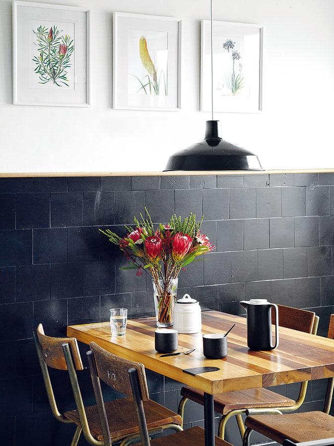 Sterilné biele obkladačky zmenil náter na tmavosivé. Obklad ukončuje jednoduchá drevená lišta, ktorá opticky rozdelila stenu – s bielou časťou, ktorú jemne oživujú obrázky rastlín od Vicki Thomasovej, kontrastuje čierna lampa, na tmavom pozadí sa zas vyníma drevený stôl.