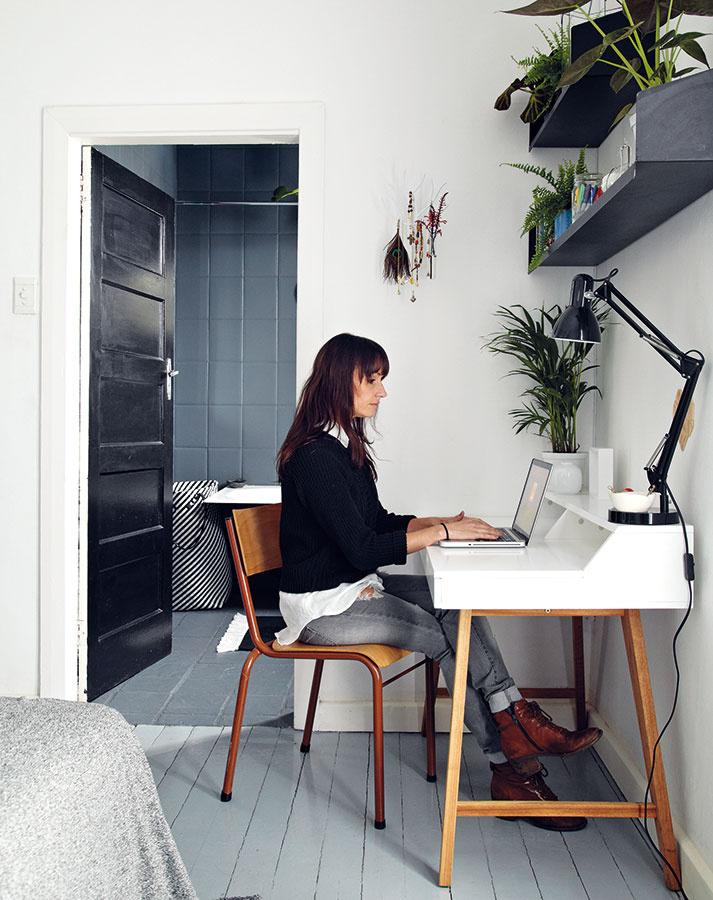 Pracovný kút v spálni. Janine umiestnila do rohu malý písací stôl a na stenu zavesila police. Rastliny, knihy a stolová lampa tvoria jeden štýlový celok, ktorý poskytuje ilúziu osobitného priestoru.