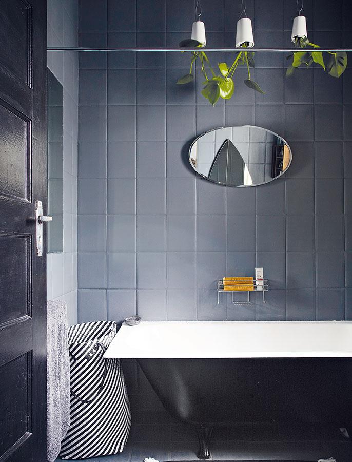 Pôvodné biele obkladačky zmizli aj v kúpeľni pod vrstvou tmavosivej farby, vaňa je teraz čierna. Zrkadlá z blšieho trhu poslúžili ako strategická pomôcka na optické rozšírenie priestoru, aj ako štýlový prvok.