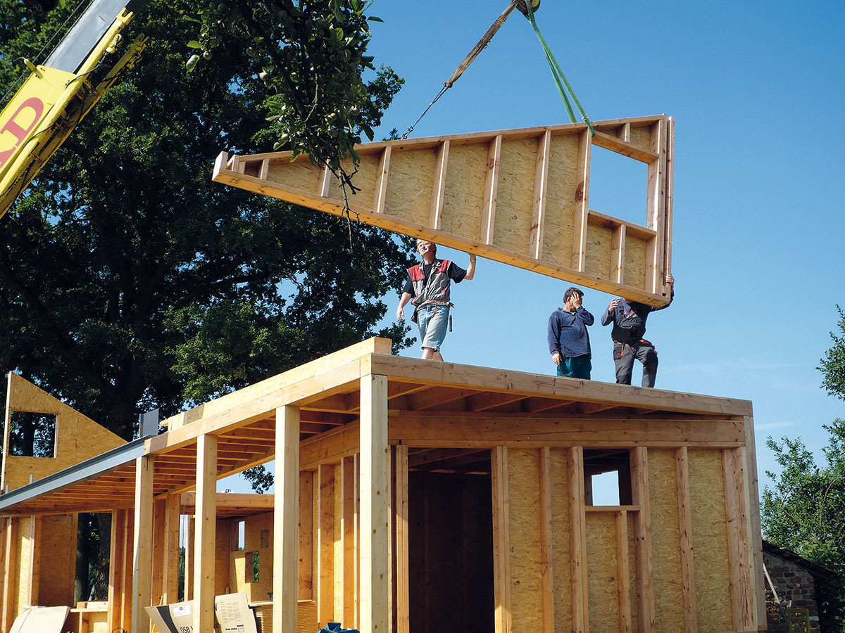 Montáž domu zdrevených panelov. Panely sa pripravia videálnych podmienkach výrobnej haly apráce na stavenisku možno naplánovať tak, aby odkryté konštrukcie nepoznačilo nepriaznivé počasie. Potrebná je však ťažká stavebná technika. Moderné technológie ako 3D počítačové modelovanie aCNC opracovanie dreva nielen zefektívňujú výrobu typových domov, ale aj umožňujú zrealizovať zložité konštrukcie na mieru.