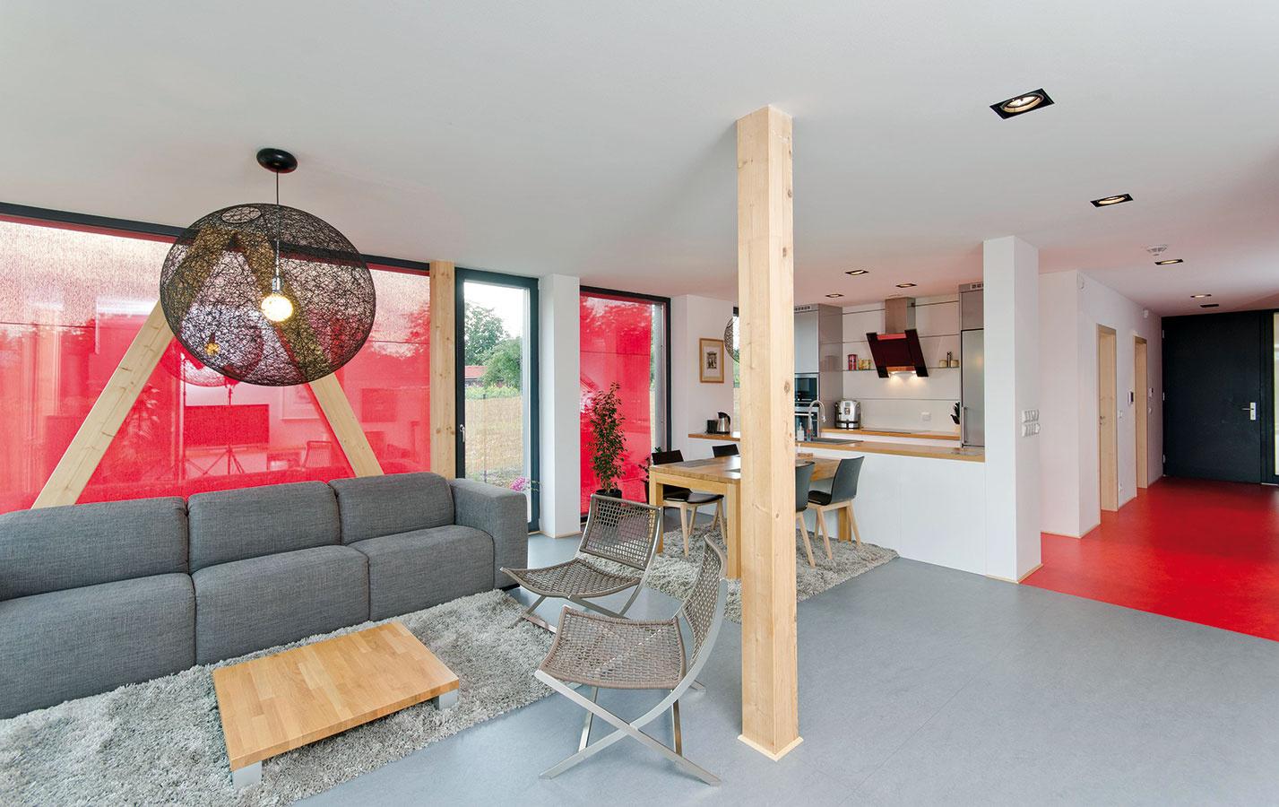 Pôsobivé kontrasty. Interiér je zariadený prevažne v jemných neutrálnych tónoch, s ktorými výrazne kontrastuje niekoľko jasne červených prvkov. Neutrálny základ, ktorý dáva vyniknúť ostatnému zariadeniu, vytvára sivá podlaha z prírodného linolea, teplá a mäkká na dotyk, a priznané konštrukčné drevo.