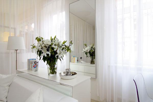 Váza s ľaliami dotvára kompozíciu bielej koženej pohovky a zrkadla, ktoré svoj horný rám zosúladilo s výškou okien.