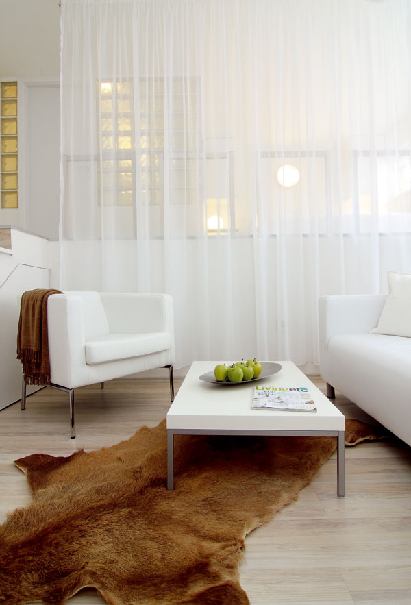 Priesvitný záves oddeľuje, ale celkom nezakrýva obrysy nočnej časti bytu.