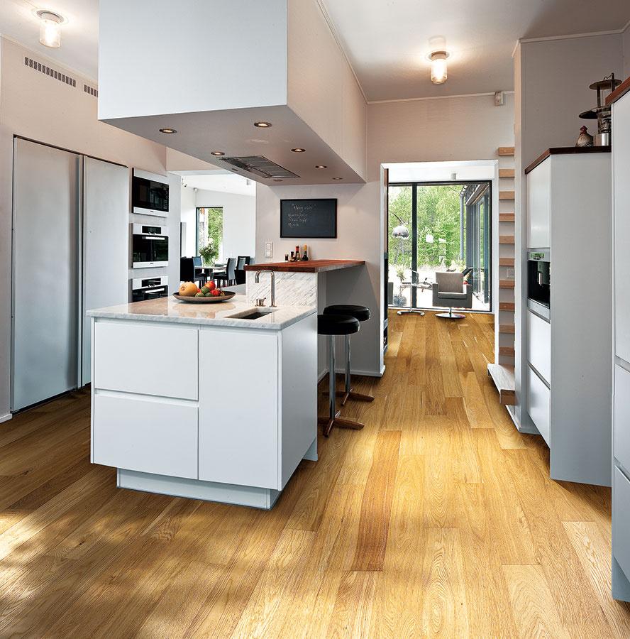 Drevené podlahy si vďaka svojej elegancii a variabilite nájdu uplatnenie v nejednej kuchyni. Pozor však dajte na kvalitné spracovanie a nepodceňte pravidelnú údržbu (drevená podlaha od značky Kährs z kolekcie Spirit Unity, 1200 × 125 mm, hrúbka 10,2 mm, zámkový spoj, dekor Reef, predáva KPP SK).