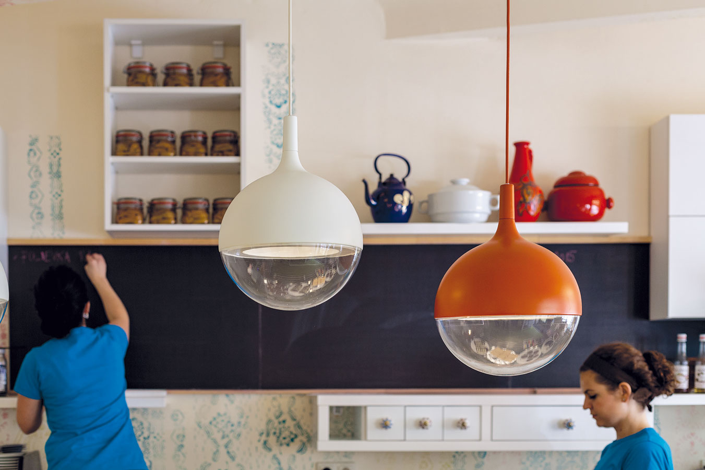 Výdajný pult anajmä kuchynská linka pôsobia absolútne domácky. Zásuvky oživujú porcelánové úchytky, zástenu nahrádza valčeková maľovka, na policiach je naukladaná keramika aporcelán. Kombinácia svietidiel rovnakého tvaru, no srôznou farebnosťou adĺžkou kábla priestor dynamizuje.