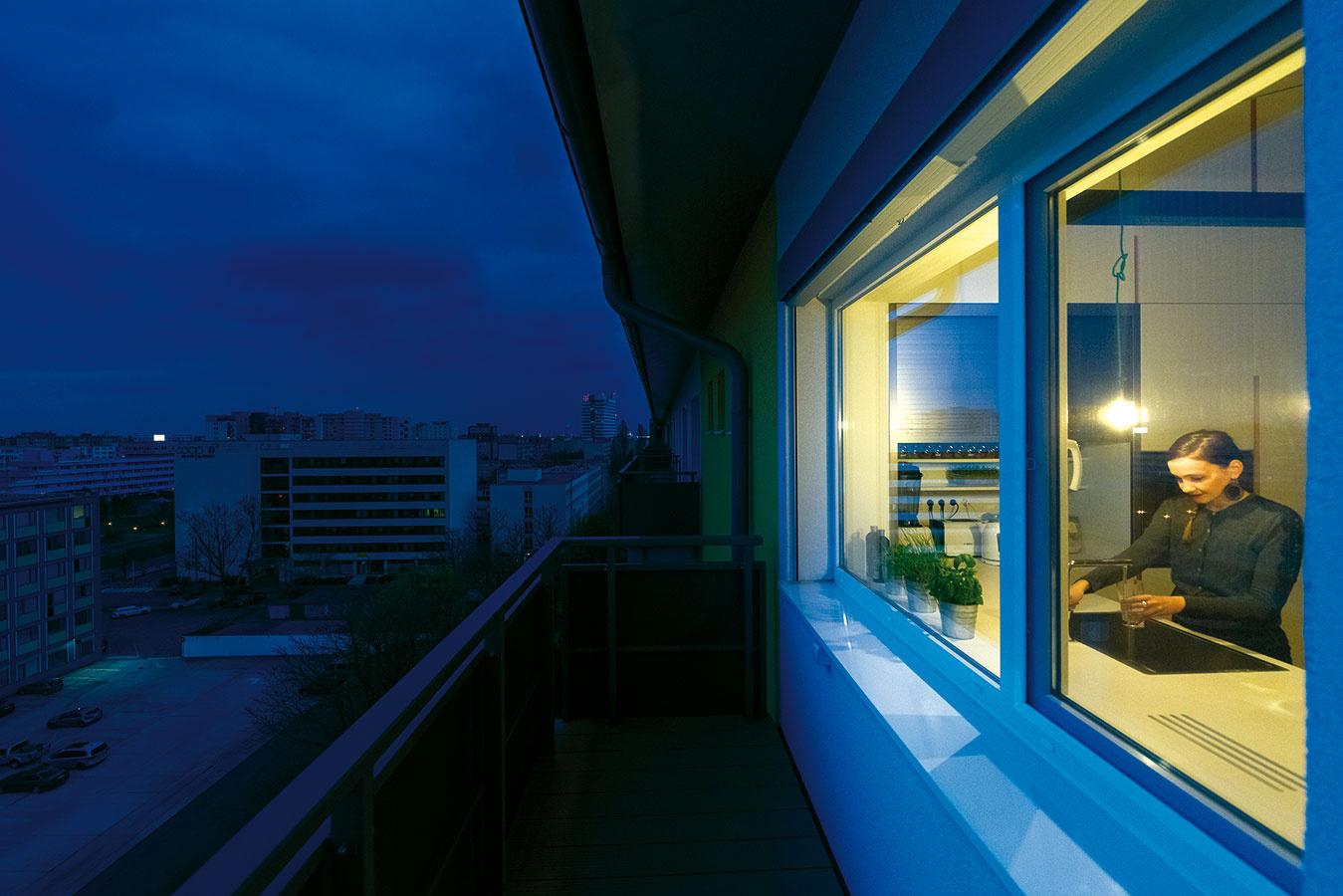 Kuchynská pracovná doska zjednoduchej bielej MDF dosky plní aj funkciu parapetu. Pri otvorenom okne poslúži ako barový pult pre terasu.