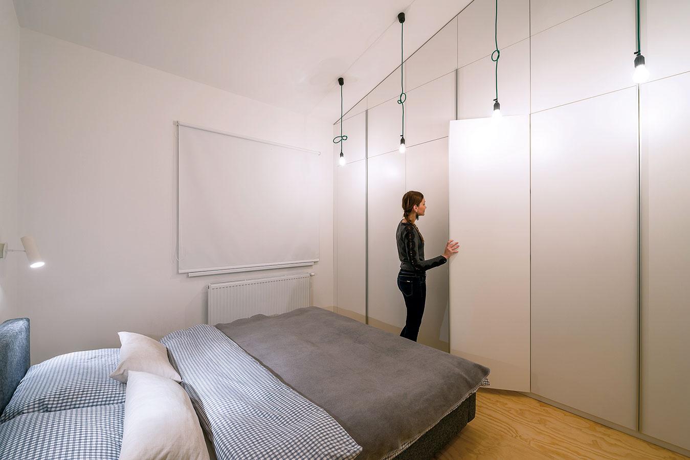 Vstavané skrine vrodičovskej spálni maximálne využívajú vysokú výšku priestoru. Materiálovo korešpondujú so zvyškom vstavaného nábytku, otváranie uľahčujú minimalistické dlhé hliníkové úchytky.