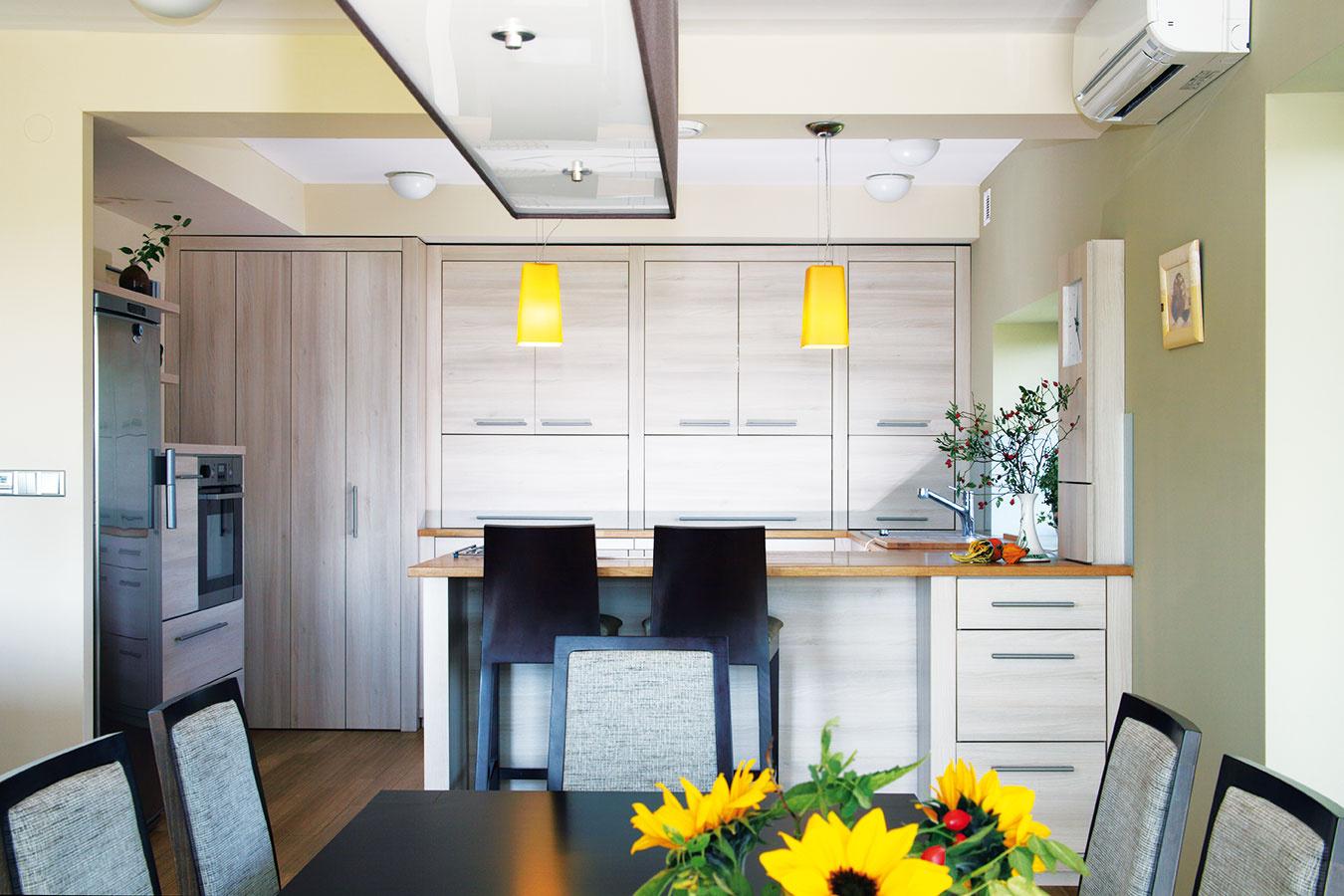 Vkuchyni by ste márne hľadali otvorené police – všetky kuchynské nevyhnutnosti sú skryté za dvierkami, vďaka čomu priestor pôsobí  čisto aúhľadne. Sviežim farebným akcentom sú žlté svietidlá nad kuchynským pultom.