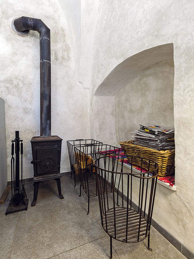 Kachle v zimných mesiacoch kaviareň prehrejú a sú nepochybne štýlovým prvkom priestoru. Kovové nádoby na drevo im vkusne sekundujú. V interiéri svojho domova ich môžete nahradiť menšími, aktuálne trendovými drôtenými košmi.