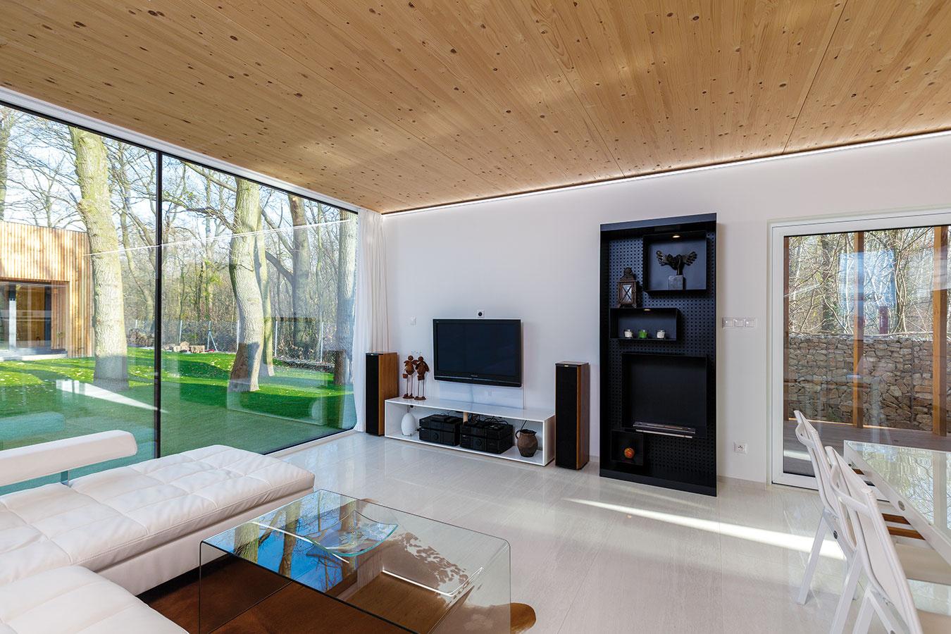Drevený strop pôsobí ako protipól k bielej gresovej podlahe. Interiér tak získal teplejší dojem.
