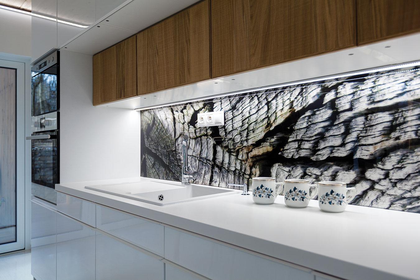 Kuchynská zástena je odkazom na prostredie, v ktorom sa dom nachádza. So stromami za oknom je tak interiér a dokonale prepojený s exteriérom.