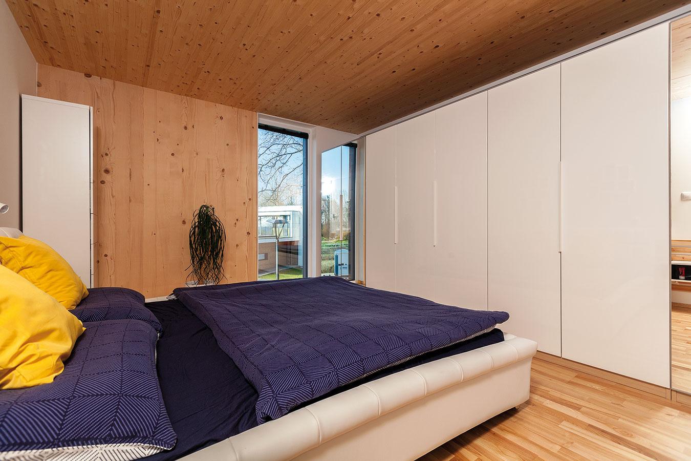 V spálni by bola prirodzene očakávaná presklená stena smerom do spoločnej záhrady. Manželia však uprednostnili väčšie súkromie a potrebu úložných priestorov, preto tento priestor využili na šatníkovú skriňu.