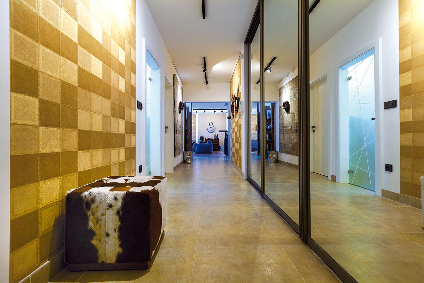 Dlhá chodba, ktorú zjednej strany lemujú zrkadlové dvere šatníka azdruhej dvere do kúpeľne ahosťovskej izby, vás privedie priamo do stredu otvoreného denného priestoru, medzi obývačku ajedáleň.