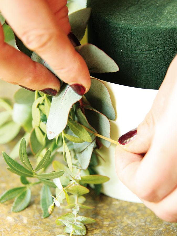 Okolo nádoby navlečte gumičku anastrihanú zeleň umiestnite striedavo pod ňu.