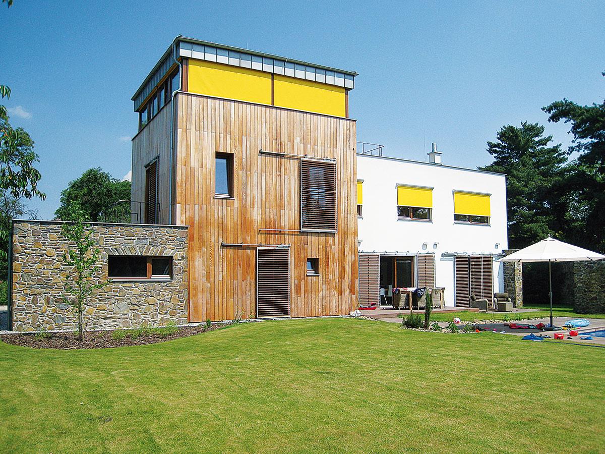 Vhodnou kombináciou tieniacich systémov možno nielen zabezpečiť pohodu vinteriéri, ale aj efektne oživiť architektúru domu. Okenice skovovým rámom adrevenou naklápacou lamelou sú tu skombinované svýraznými žltými screenovými roletami.