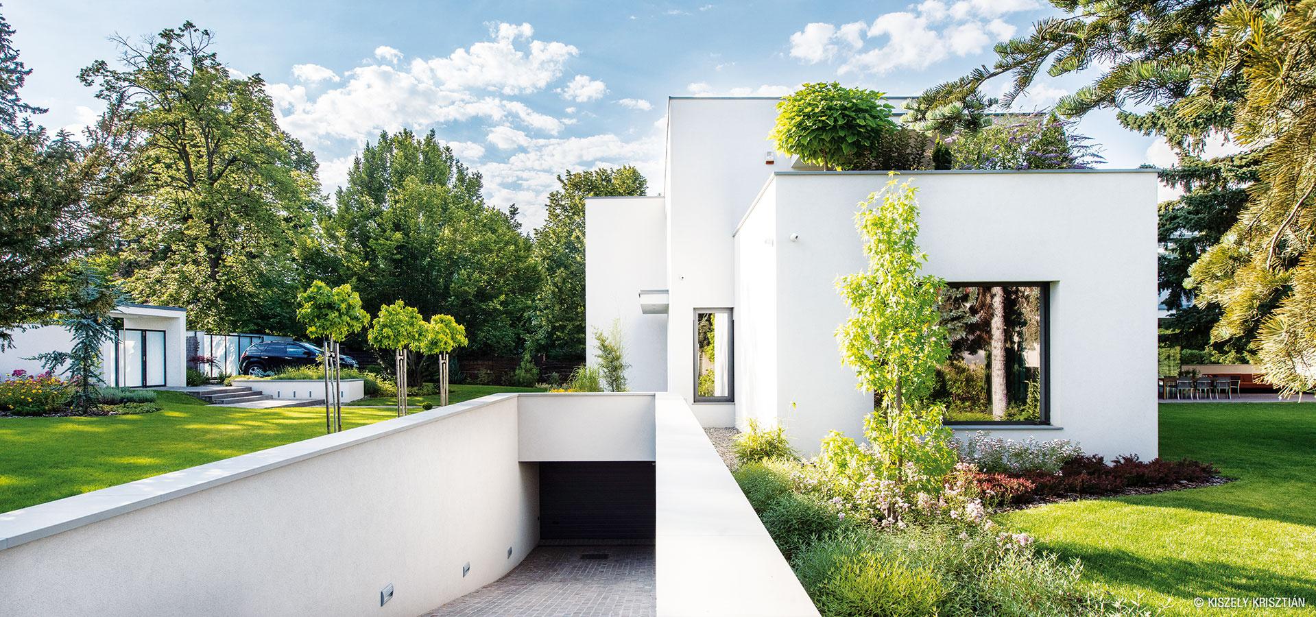 Technické zázemie so svojským vstupom je dôkazom toho, ako sa tvarovo jednoduché časti budovy na seba zaujímavo vrstvia, prelínajú so stromami afunkčne odlišujú.