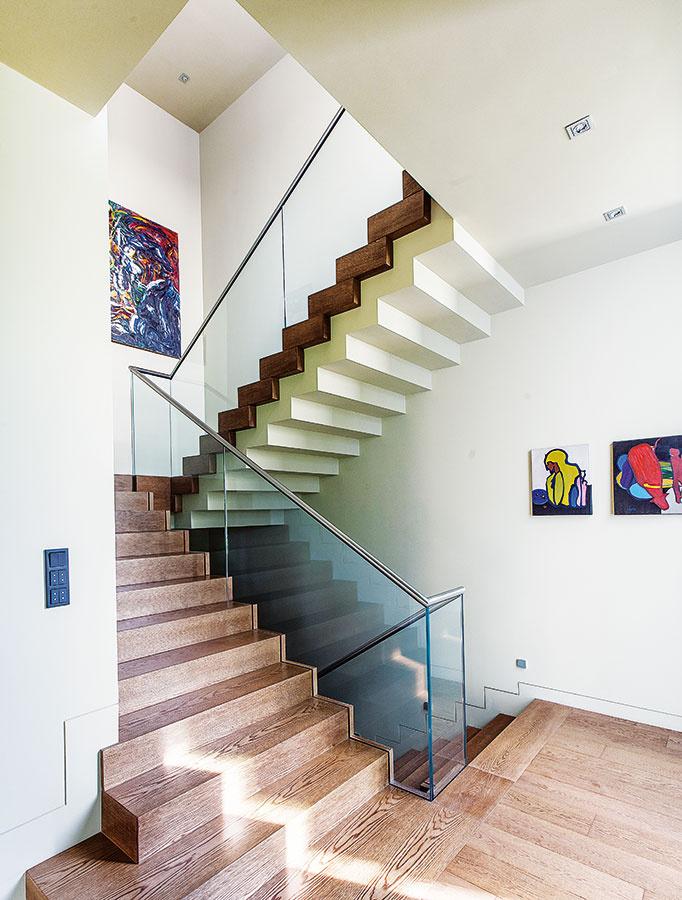 Schodisková galéria. Neutrálnu farebnosť adominanciu pravidelného štvoruholníka na schodisku dotvárajú výrazné abstraktné  obrazy zo zbierky domáceho pána.