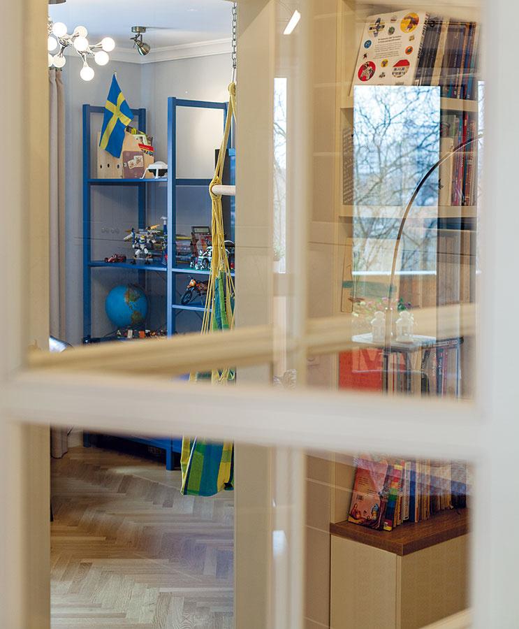 Efektný prvok. Veľká zasklená stena, ktorá oddeľuje chodbu od kuchyne ajedálne, je vhlavnom priestore bytu účinným pohľadovým magnetom. Efektný je aj priehľad do chodby – knižnice.