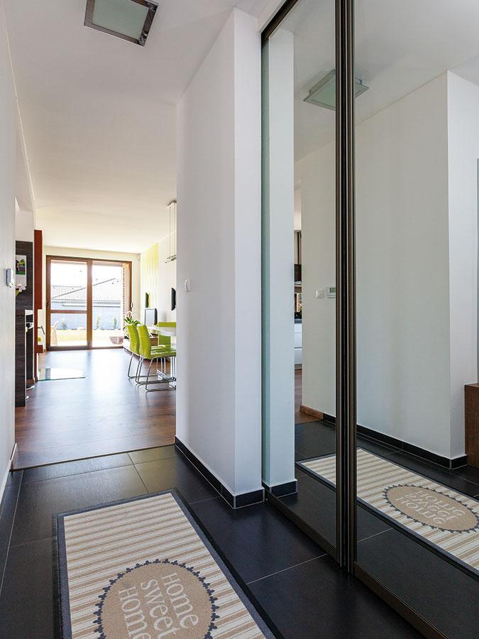 Bez skríň. Táto originálna požiadavka manželov výrazne ovplyvnila dispozíciu domu – pri každej zizieb je totiž samostatný šatník. Praktická miestnôstka nechýba ani vedľa predsiene, kde sa zrkadlové dvere šatníka zároveň postarali ooptické rozšírenie priestoru.