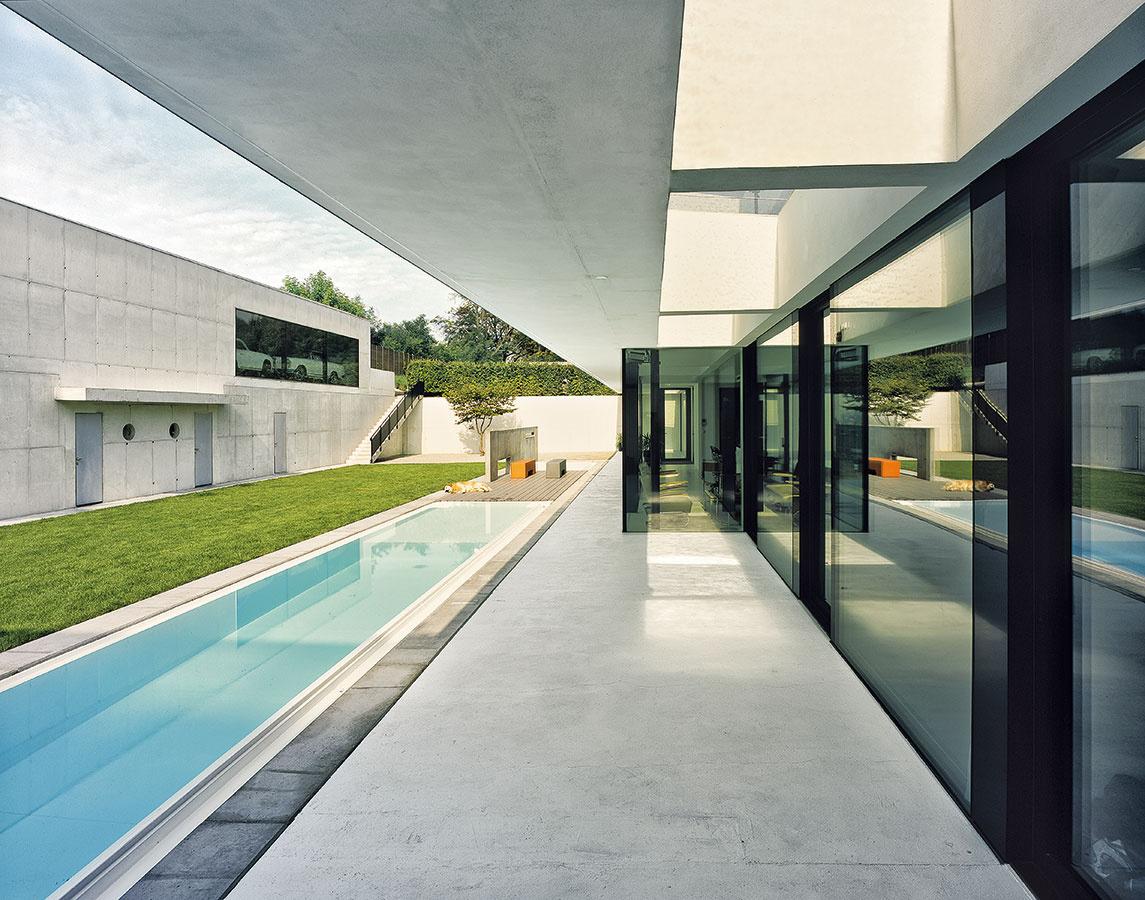 S dovolenkovou atmosférou. Dom lemuje po celej dĺžke terasa, na ktorú nadväzuje blok sdvoma bazénmi so slanou vodou a mólom s ležadlami na opaľovanie. Dlhší z bazénov je aj svojou hĺbkou určený na plávanie, druhý, kratší aplytší, je najmä dekoratívny.