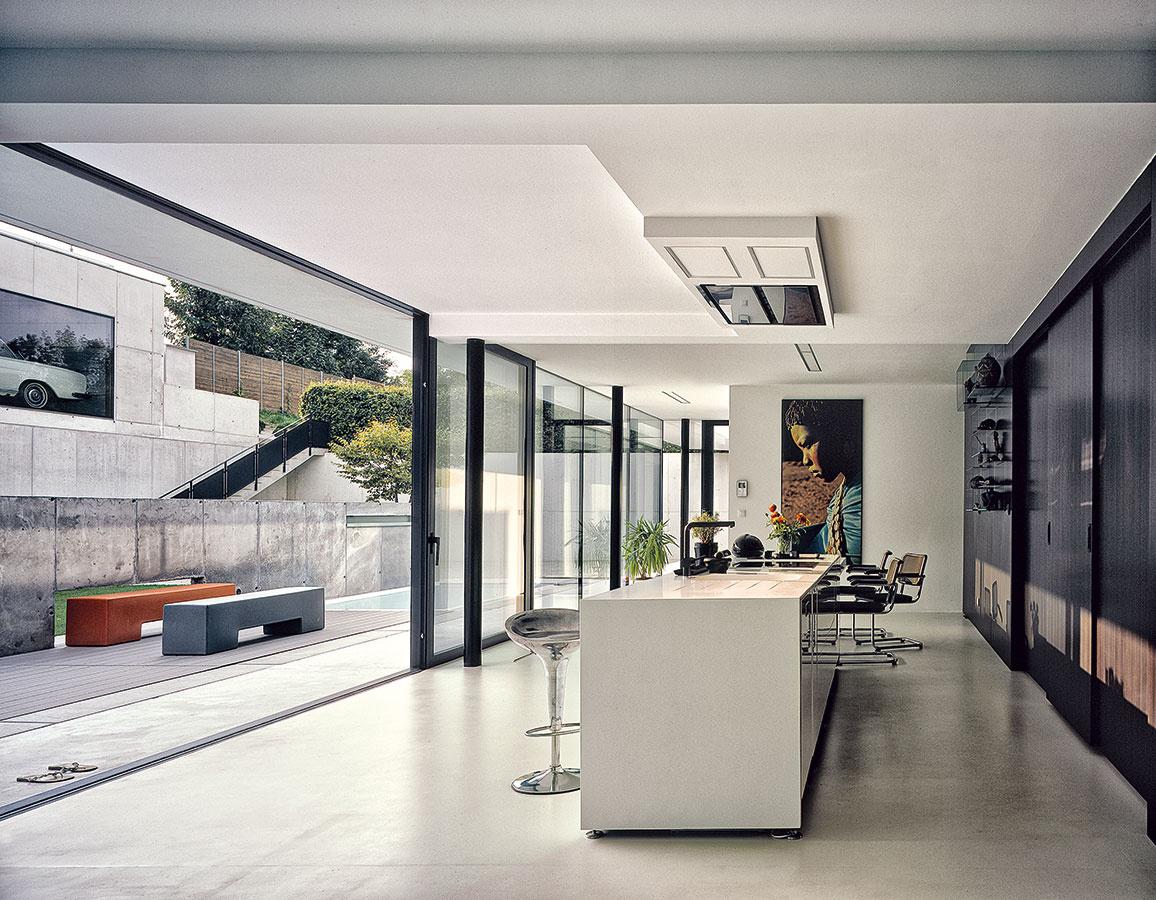 Vduchu kontrastov. Vinteriéri sa stretáva tieň so slnkom, tmavé so svetlým – palisandrová dyha na zadnej stene kontrastuje sčistým odtieňom bielej omietky na bočných stenách astrope. Všetok nábytok sa vyrábal na mieru.