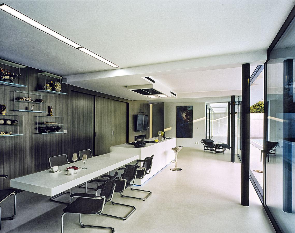Vmene elegancie. Čierne stoličky vjedálenskej časti sa farebne prikláňajú ktmavej dyhe na zadnej stene kuchyne. Za posuvnými dverami sa tu šikovne skryli chladnička, rúra aďalšie dôležité súčasti nevyhnutného technického vybavenia.