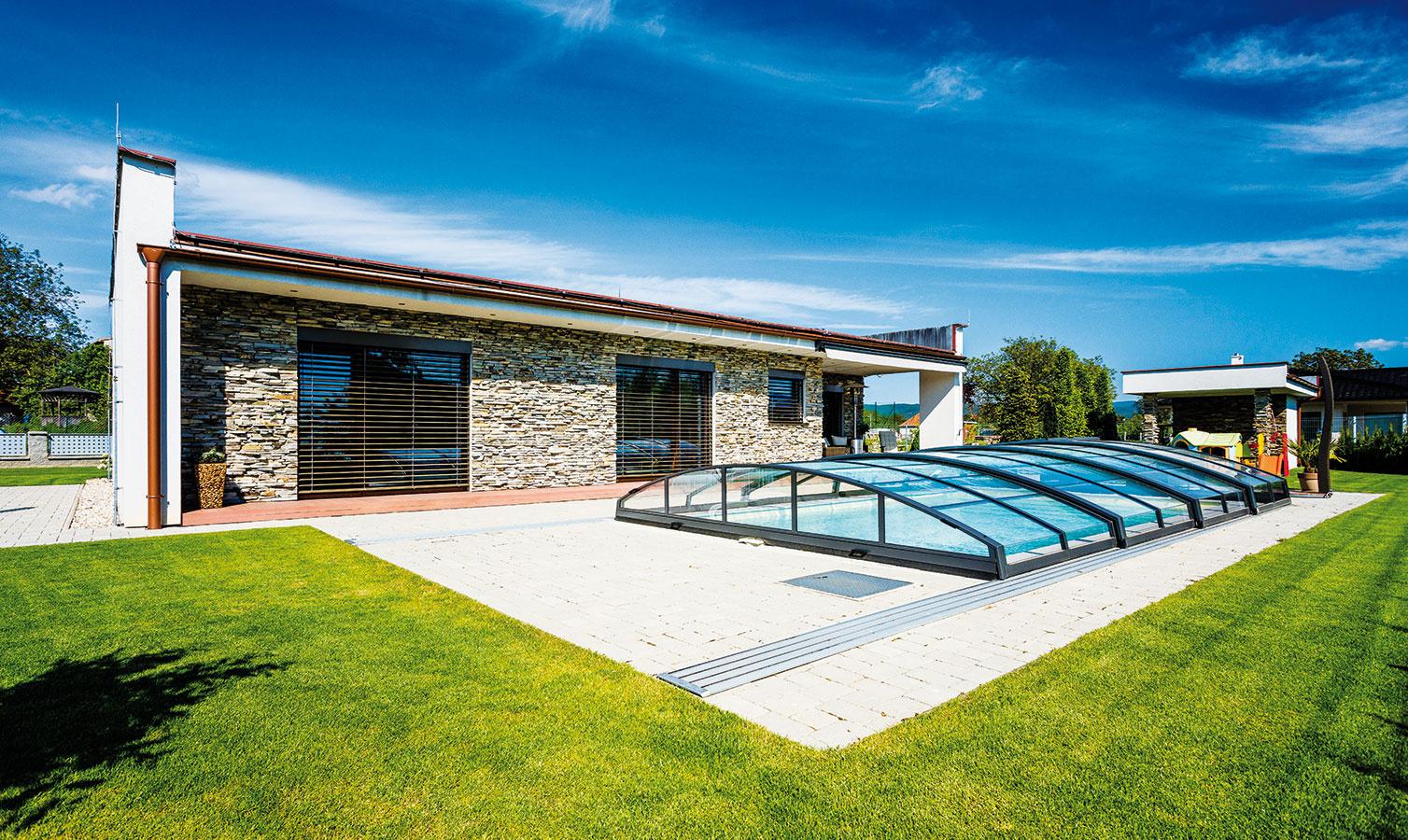 Za domom, vjužne orientovanej záhrade, do ktorej sa obracajú okná všetkých izieb okrem pracovne, sa naplno relaxuje. Záhrade dominuje bazén uprostred udržiavaného trávnika, ktorý spolu sterasou, fasádnym obkladom zrezaného prírodného kameňa asivou dlažbou navodzuje pocit dovolenkového apartmánu.