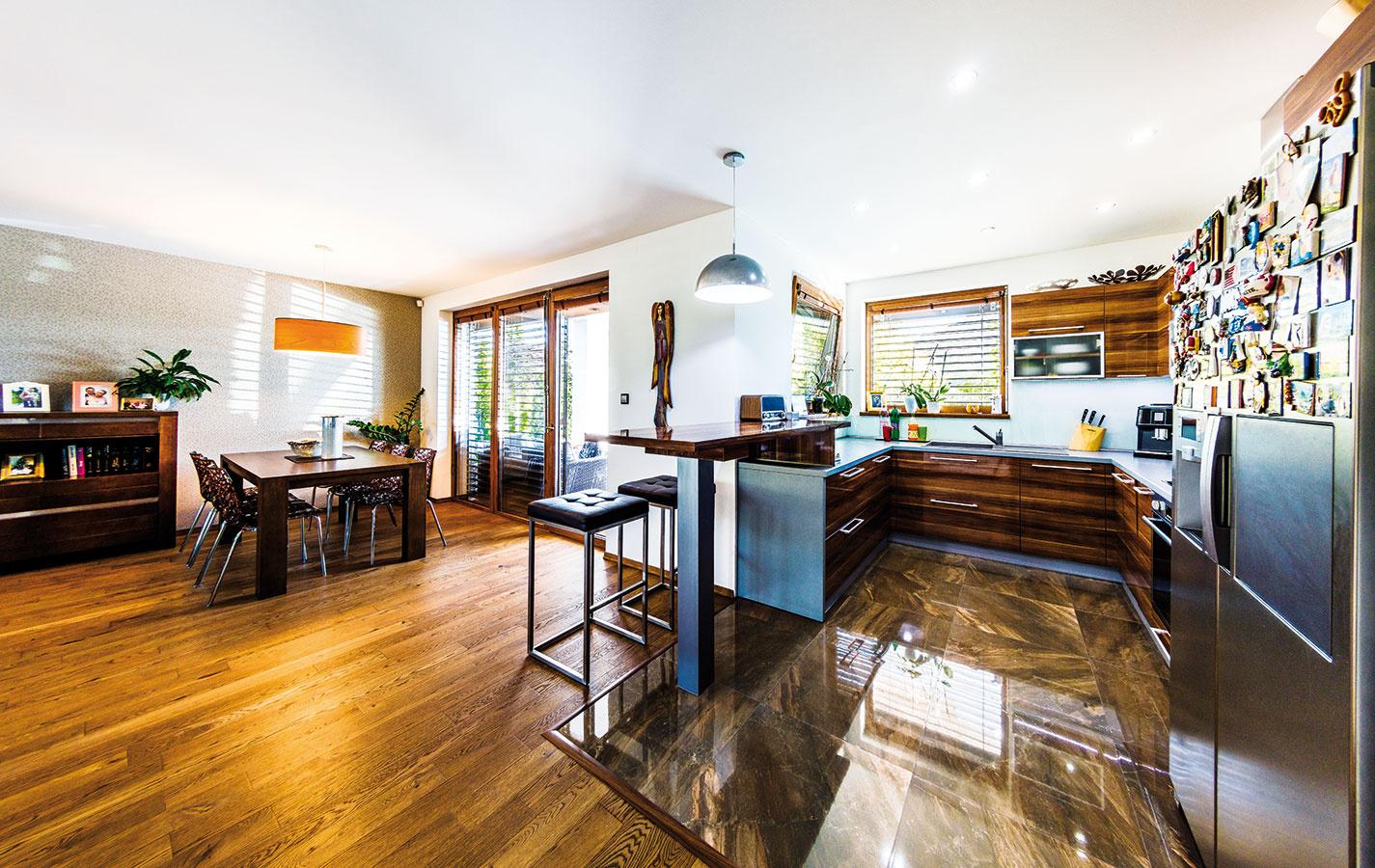 """Srdcom domu je otvorený priestor sobývačkou akuchyňou, ikeď vpôvodnom katalógovom projekte bola kuchyňa navrhnutá ako samostatná miestnosť skomorou. """"Nechceli sme kuchyňu odrezať od centra diania. Navyše, nezmestila by sa nám do nej chladnička, ajdetská izba by bola oniečo menšia,"""" vysvetľuje praktické zmeny vdispozícii majiteľ."""