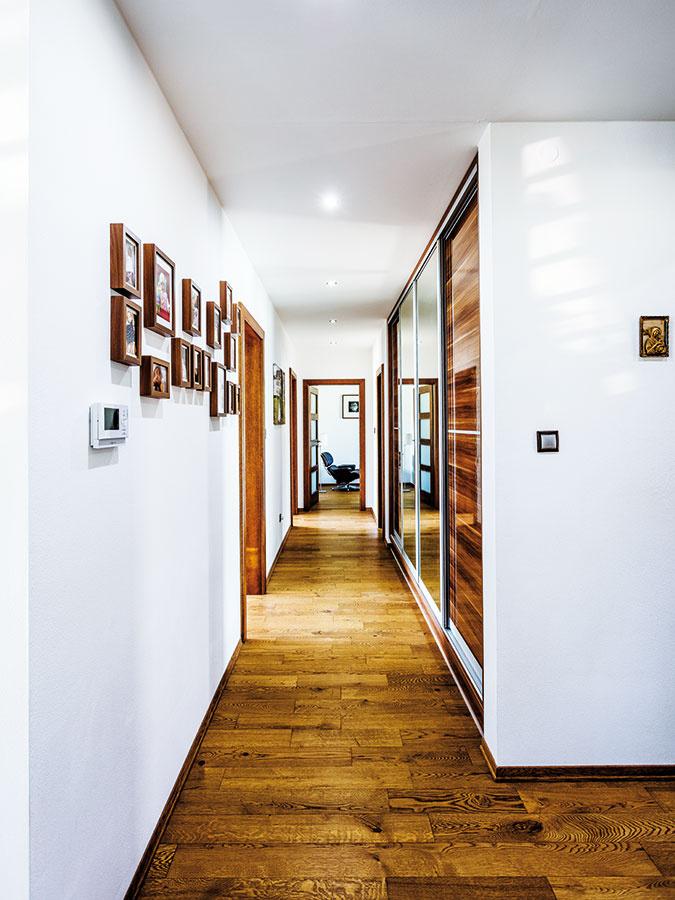 Kontrast hnedých tónov dreva abielej farby stien je hlavnou témou interiérov vcelom dome, atmosféru aj kompozíciu dotvárajú rodinné fotografie. Praktické vstavané skrine vyrobené na mieru sú vchodbe aj vspálňach, majiteľka by však uvítala omnoho viac odkladacích priestorov, napríklad komoru alebo špajzu.