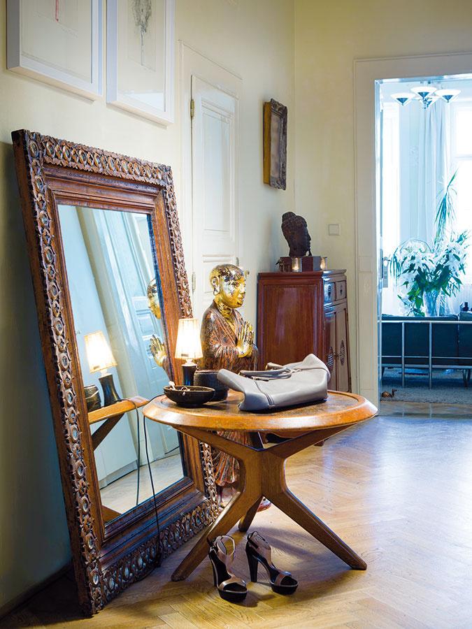 """Socha chrámového """"vítača"""" zVietnamu tematicky zaujala miesto vpredsieni. Zátišie dopĺňa ťažké starožitné zrkadlo zIndie ačeský retro stolík, ktorý zachránila Monika zkamarátkinej pivnice."""