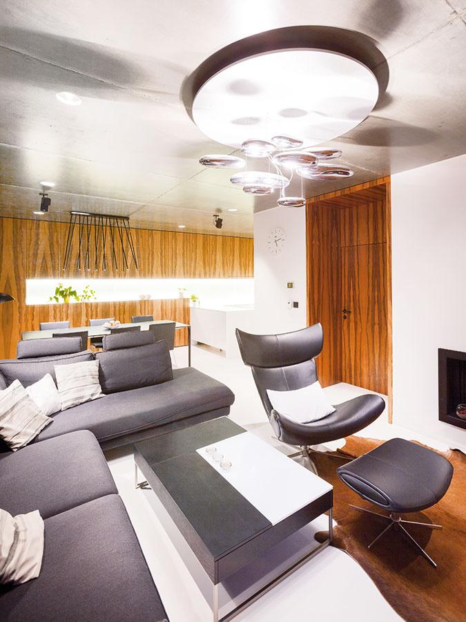 Moderný charakter dennej časti určuje predovšetkým priznaný lakovaný železobetónový strop, ktorý bol prianím domáceho pána. Strop zaujímavo kontrastuje s bielou podlahou, pričom oba prvky vzájomne prepája drevená dyha.