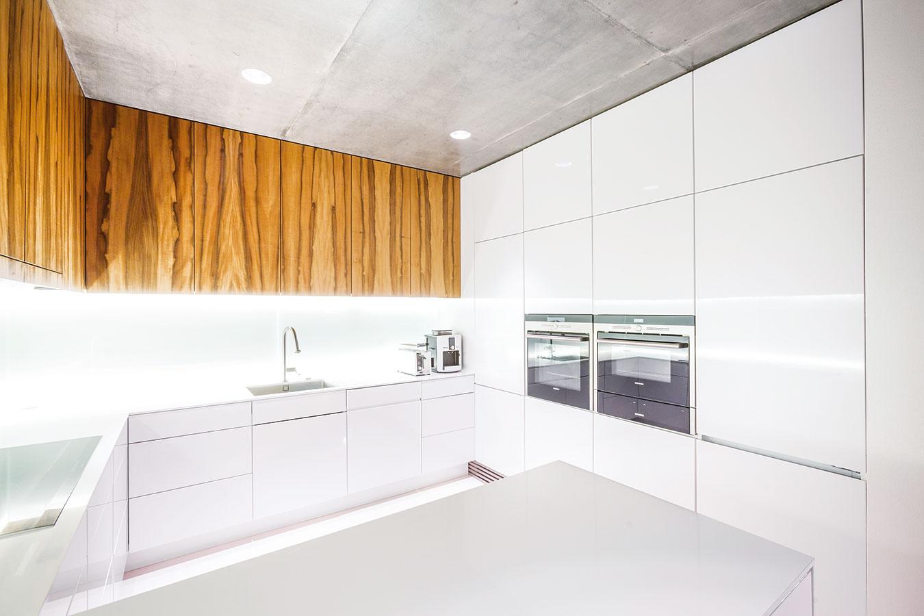 V kuchyni by ste márne hľadali otvorené police. Spodné skrinky sú biele a vyhotovené v aktuálne obľúbenom vysokom lesku. Dvierka horných skriniek tvorí dyha z indickej jablone, ktorá sa opakuje v celej dennej časti.