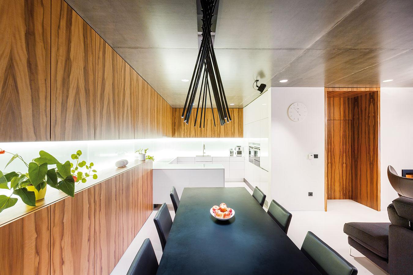 Uzavreté police v jedálenskej časti sú priamym pokračovaním kuchynskej linky a slúžia na uskladnenie nevyhnutností. Opakujúci sa materiál dodáva neveľkému priestoru zaujímavý rozmer.