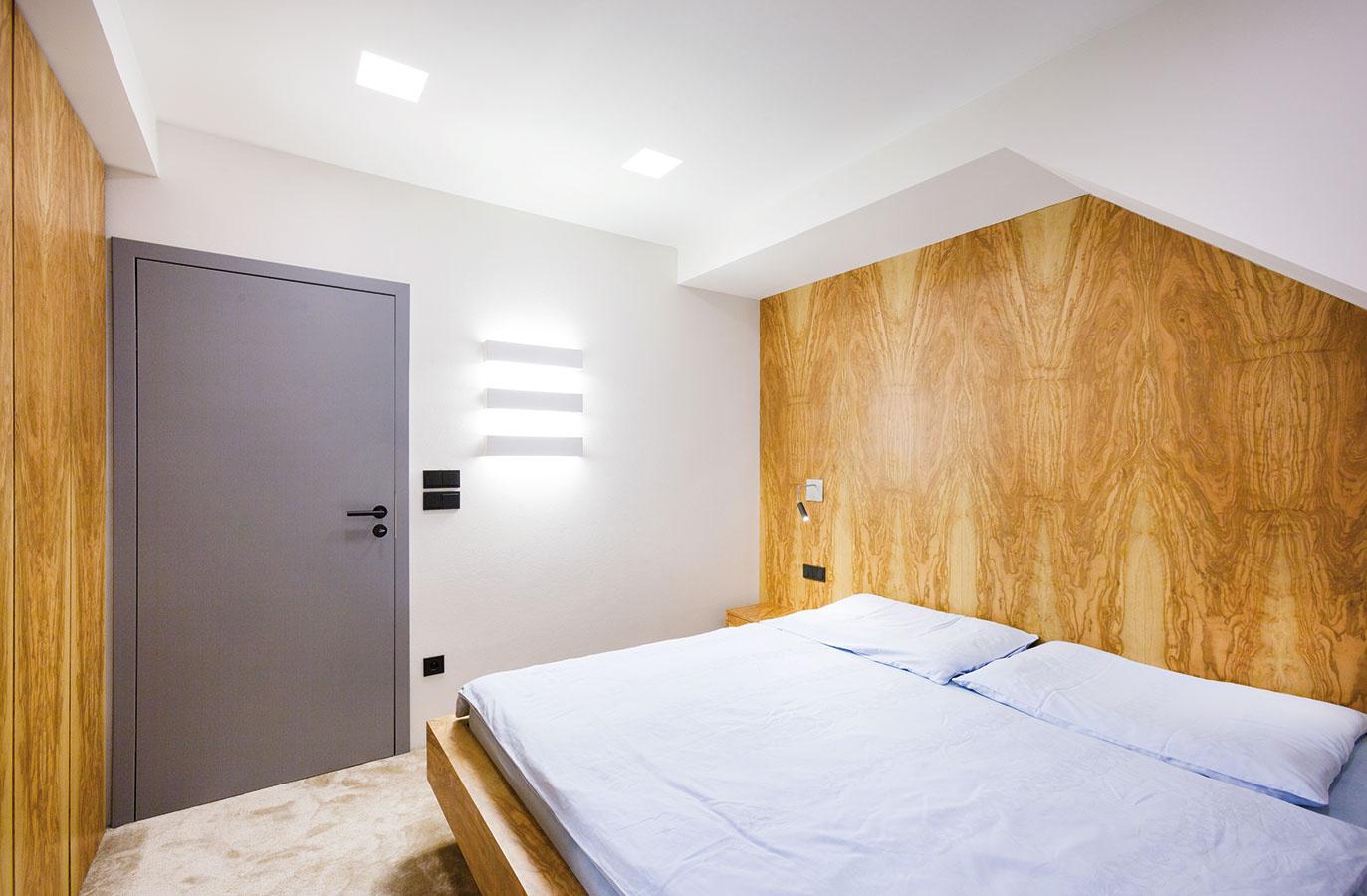 Všetok nábytok v spálni vrátane okenného parapetu je materiálovo zjednotený olivovou dyhou. Architekti sa pri jej návrhu voľne inšpirovali konceptom olivového hája.