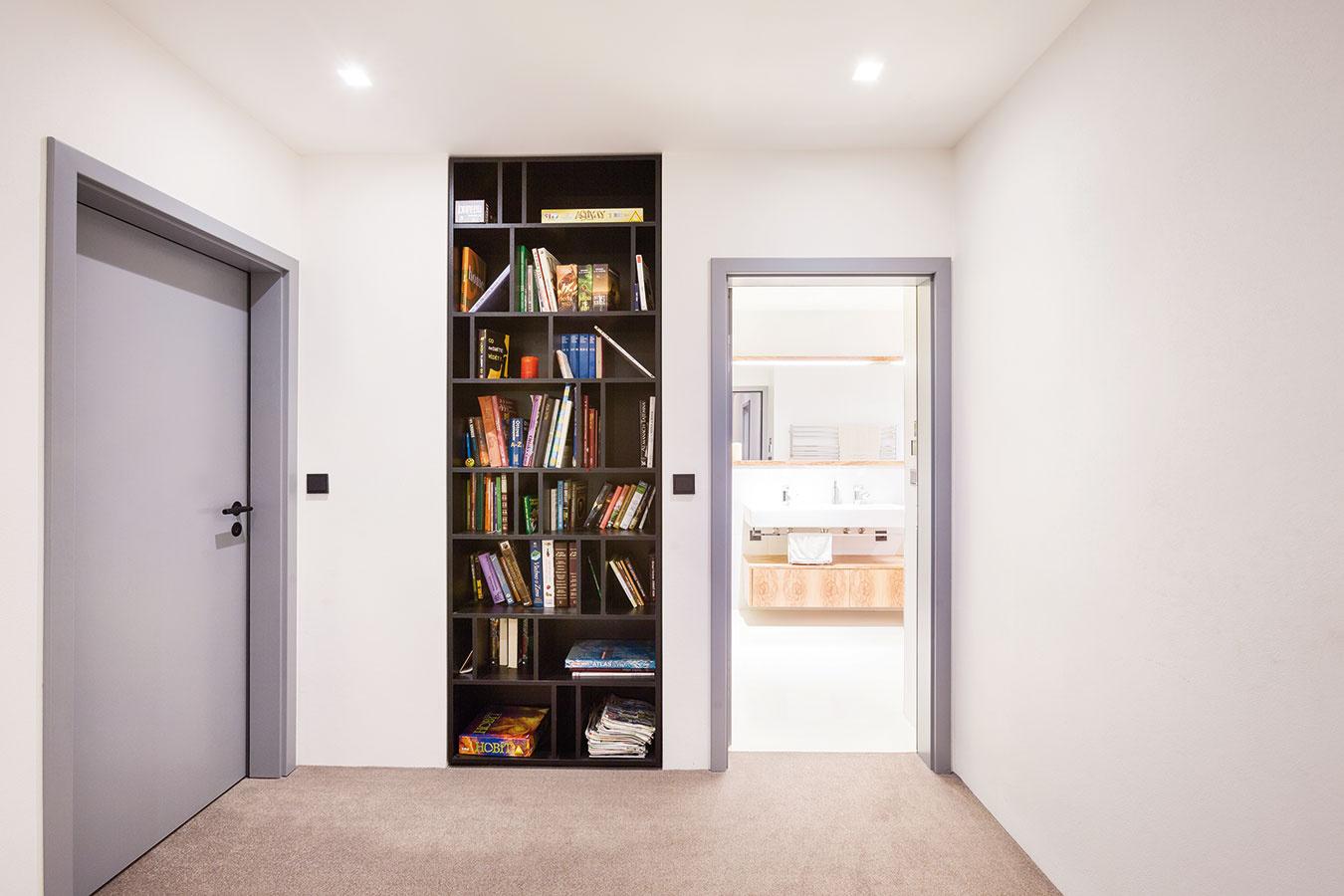 Na chodbe vznikol priestor na zabudovanú policu, ktorá slúži ako knižnica. Farby kníh či obalov spoločenských hier ju oživujú a dynamizujú.