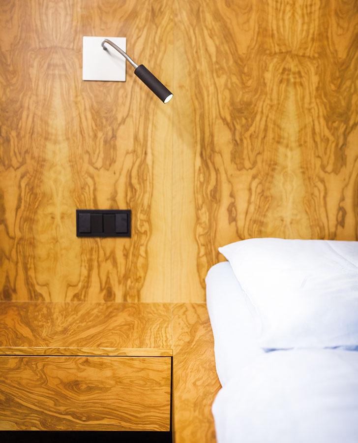 Minimalistické nočné lampy sú zabudované priamo do drevenej zásteny.