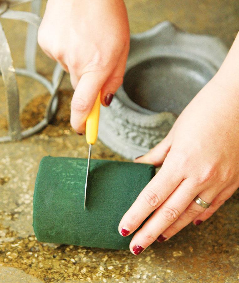 1 Namočenú aranžérsku hmotu si narežte na potrebnú veľkosť (asi 5 cm) aumiestnite ju na keramickú podnož korunky. Vrchnú kovovú časť korunky položte na tú keramickú azačnite saranžovaním.