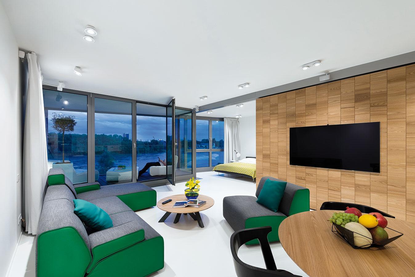 Maximálne otvorená dispozícia. Pôvodne otvorenú dennú zónu – obývačku spojenú skuchyňou ajedálňou – prepojili pomocou posuvnej steny aj so spálňou, tak, aby byt poskytol maximum využiteľného priestoru aj aby sa naplno využil exkluzívny výhľad.