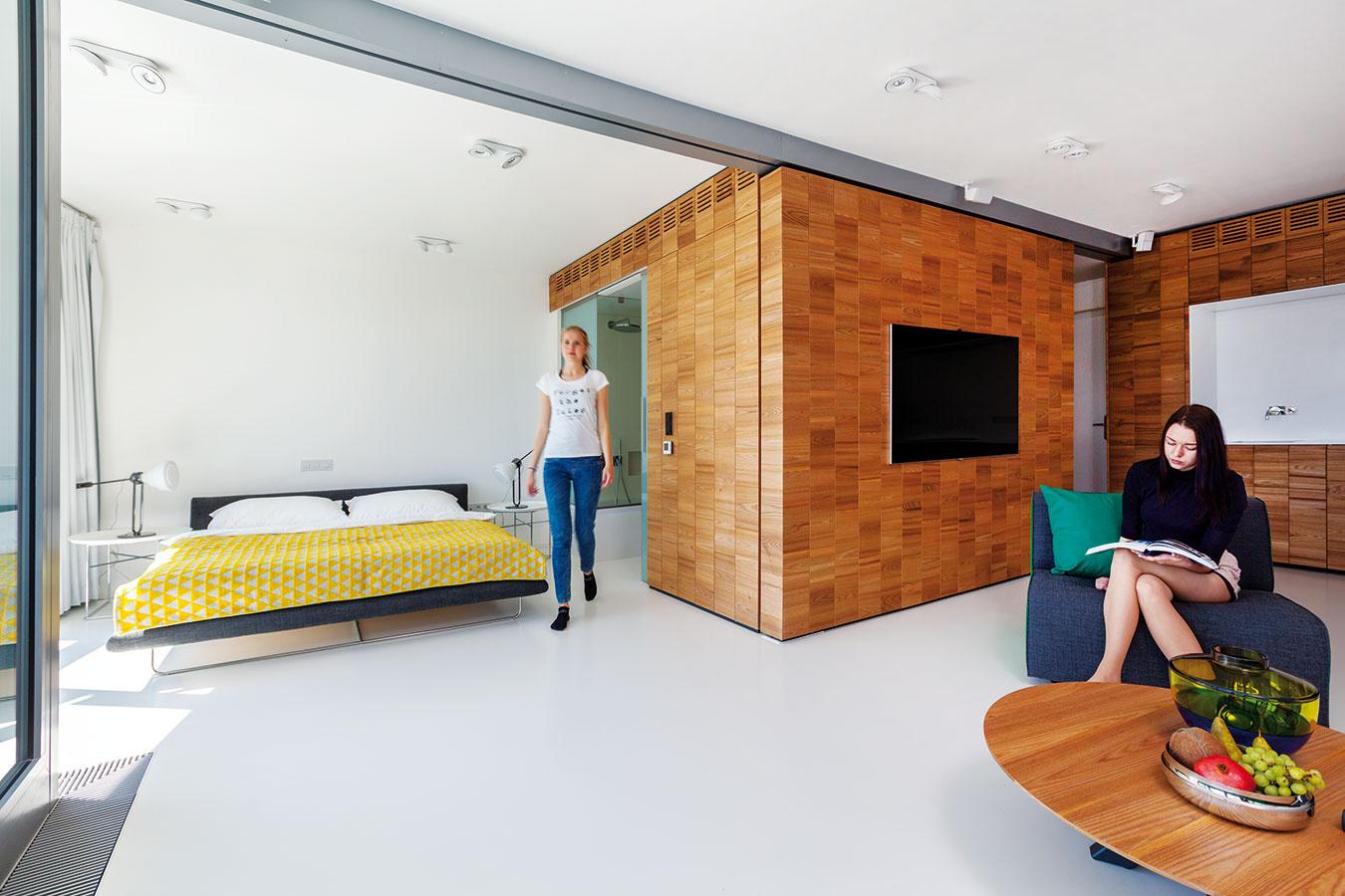 Stena vpohybe. Priechod zobývačky do spálne sa dá uzavrieť posuvnou drevenou stenou, ktorá má tri polohy – otvorenú, zatvorenú astrednú s priechodom všírke bežných dverí. Pri úplnom otvorení sa nočná zóna spojí sdennou avznikne pôsobivý obytný priestor srozlohou 60 m2.