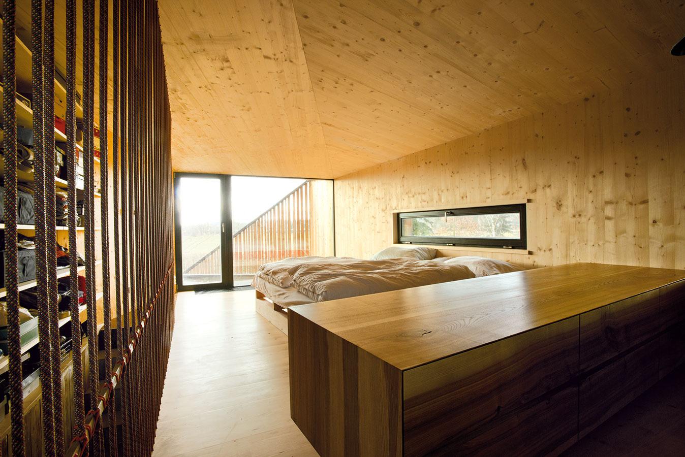 Vrodičovskej spálni na poschodí sa našlo miesto aj na zaujímavý otvorený šatník apracovný stôl. Zmateriálov tu rovnako ako vcelom dome dominuje drevo.