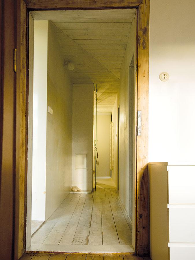 Úzka chodba na prízemí prepája detské izby skúpeľňou. Príjemnú atmosféru podčiarkuje na bielo natretá podlaha astrop, ktorý nájdete aj vmiestnosti združujúcej kuchyňu, jedáleň aobývaciu izbu.
