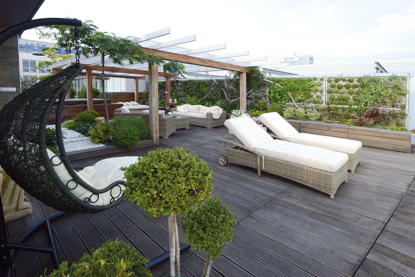 Na terase na najvyššom podlaží navrhli architekti exoticky pôsobiacu oázu oddychu, ktorej rámec vytvorila zelená stena. Podlahu ztíkového dreva oživujú vyvýšené miesta osadené zeleňou, nechýba pohodlný ratanový nábytok ani vírivka.