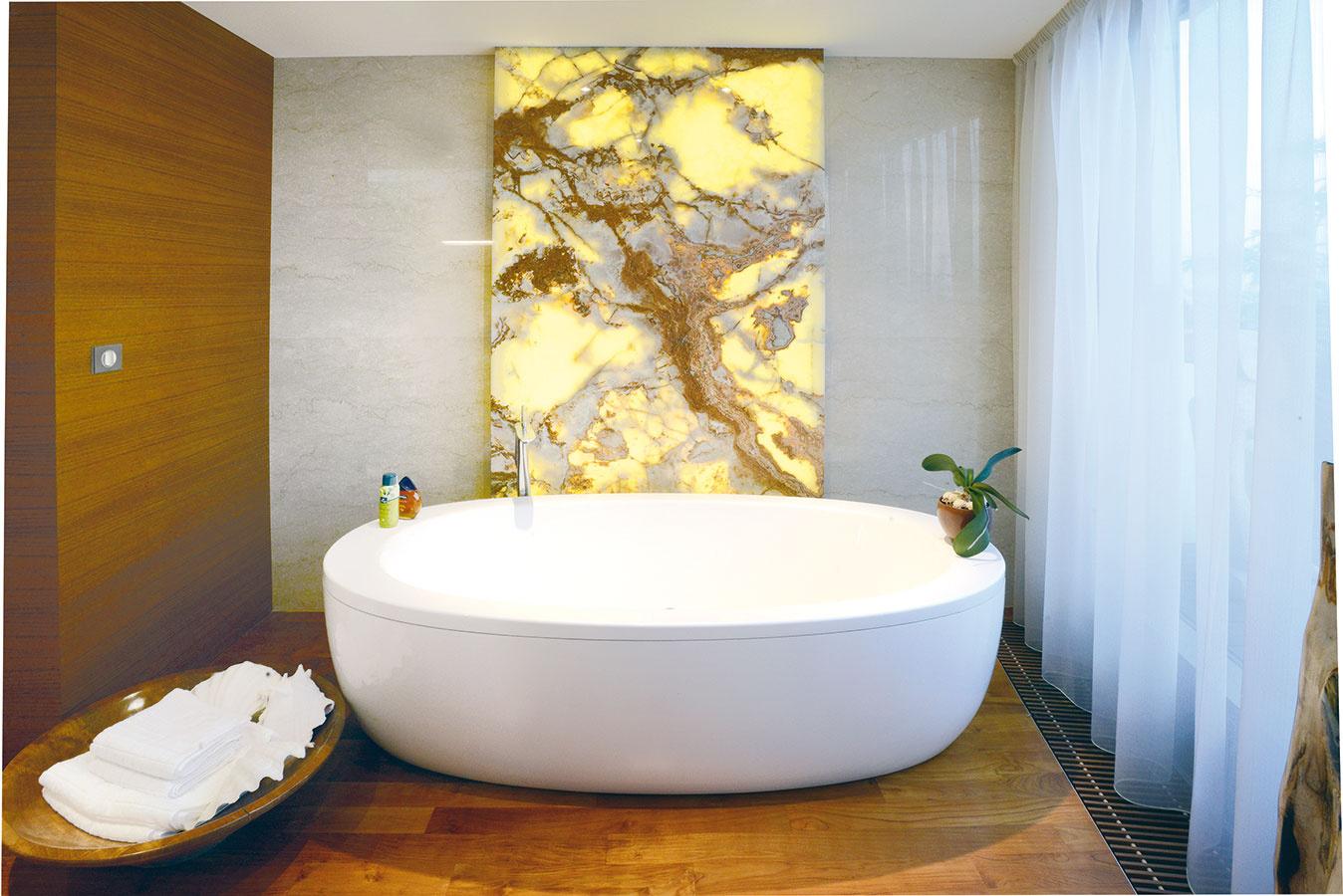 Drevo akameň. Na stenách sa drevo strieda skamenným obkladom. Efektné akcenty vytvárajú podsvietené platne ónyxu, ktoré boli želaním domácej panej. Architekti si dali na výbere jednotlivých tabúľ záležať – na väčších plochách kresba žíl nadväzuje tak, aby vznikol efekt jediného kusa kameňa.